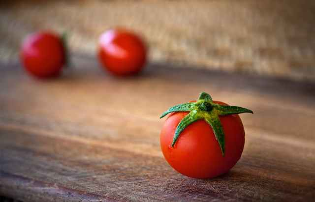 close up of tomatoes on wooden table